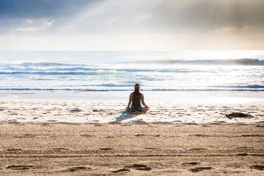 person meditating on the beach for Gulf Breeze Recovery non 12 step holistic drug rehab