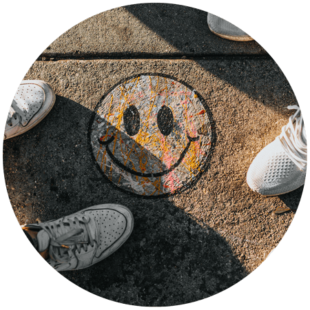 "photo of chalk smiley face drawn on the sidewalk viewed in POV from above by general public for a blog article entitled ""5 benefits of being grateful"" for Gulf Breeze Recovery a holistic non 12 step holistic drug rehab"