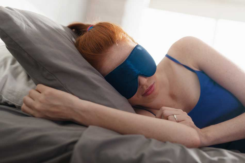 woman-in-bed-sleeping-with-sleep-mask-on-eyes-950px